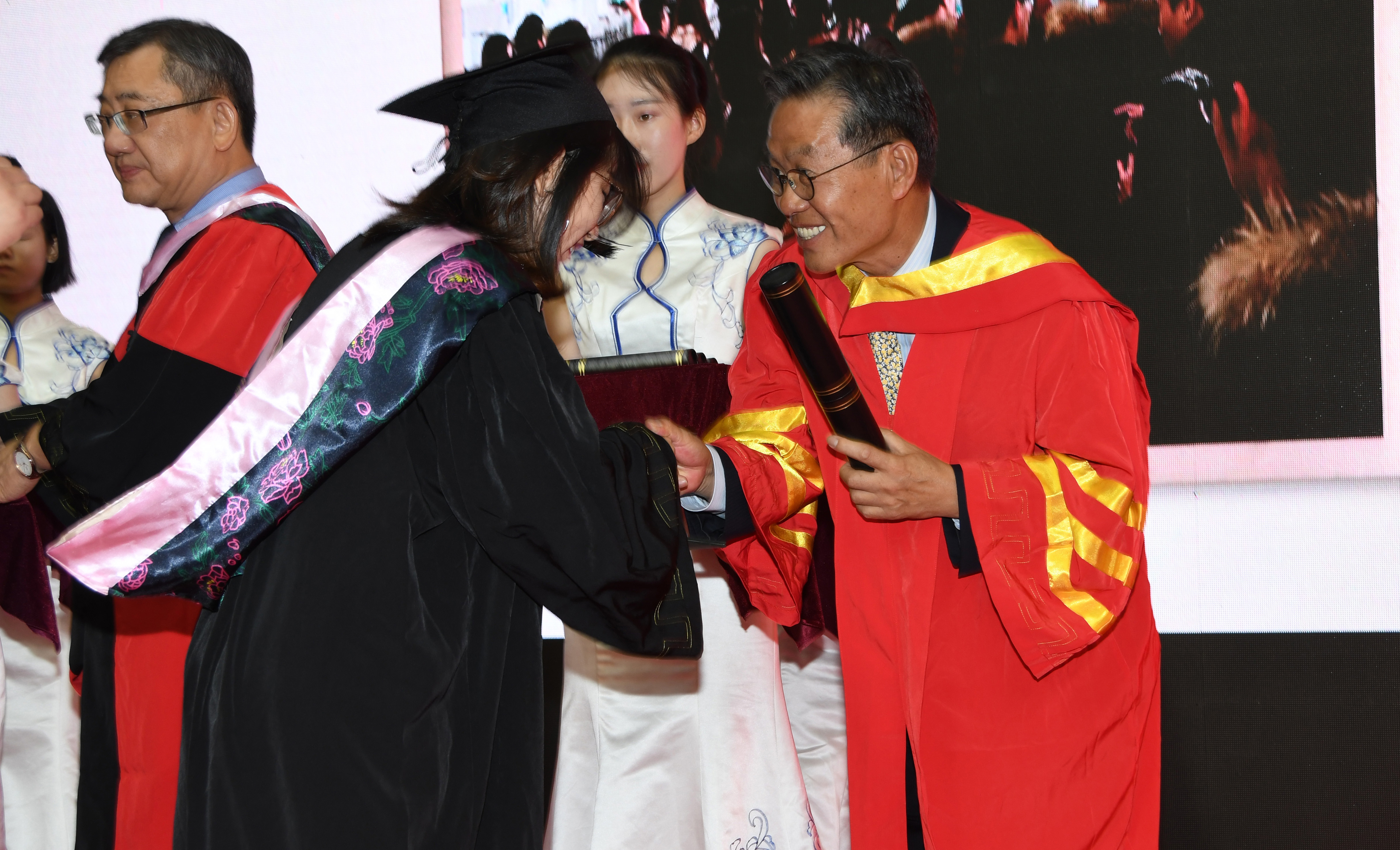 Dr. Youngski Kwak, DSU professor of accounting, presents a diploma to one of the graduates.