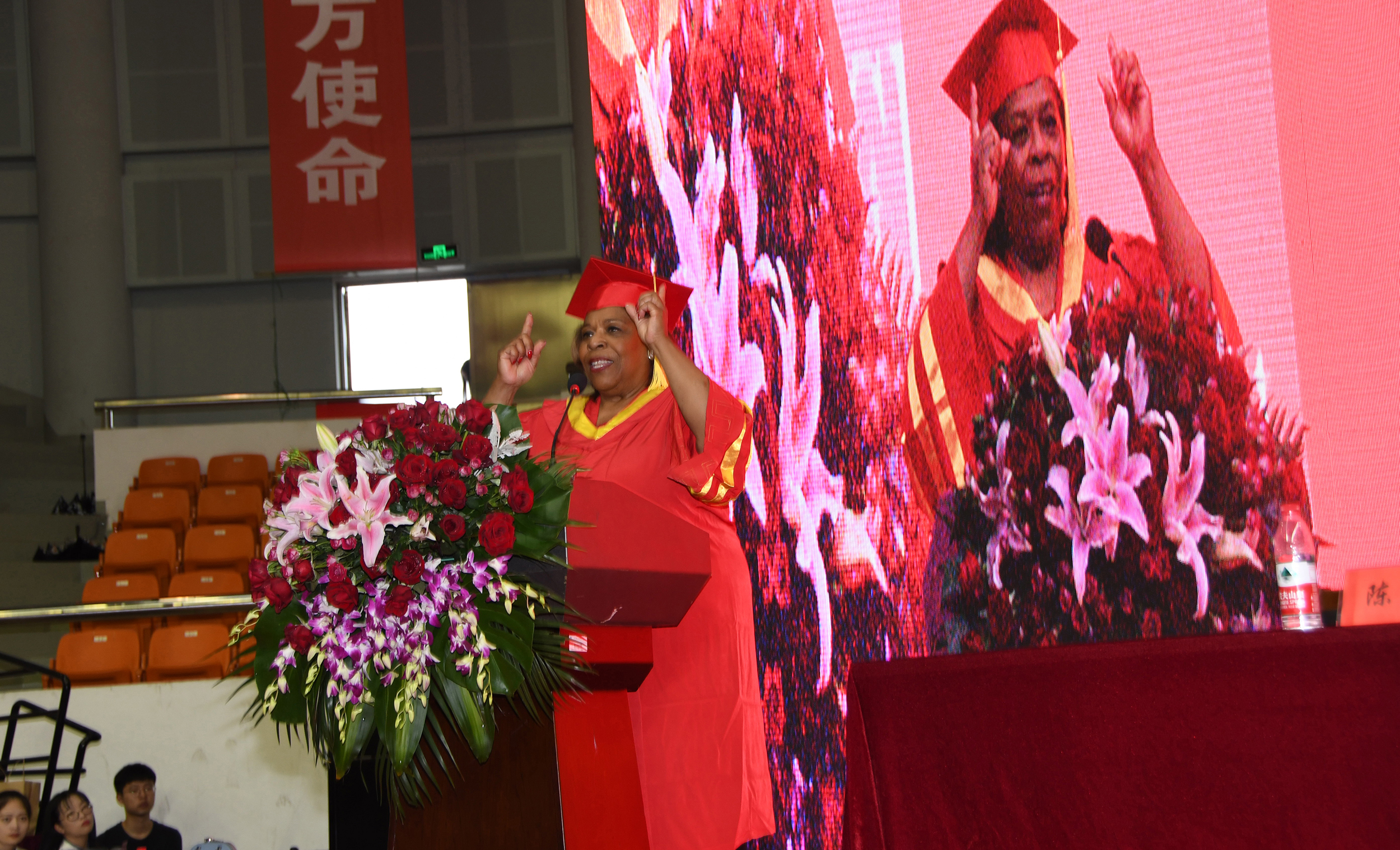 Dr. Wilma Mishoe gives her Commencement address while a larger-than-life image of her lights up the stage behind her.