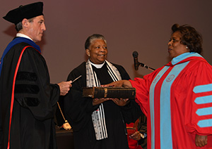 Gov. John Carney administers the oath of office to Dr. Mishoe, while her sister Rev. Rita Paige holds the bible.