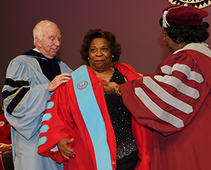 Dr. Donald Ross (l), founder of Wilmington Univ., and Dr. Thelma Thompson, former UMES president place her new robe on.