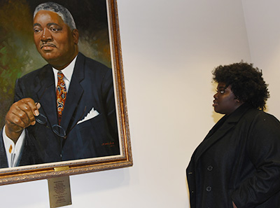 Carter at the portrait of the late Sen. Herman Holloway, sponsor of the 1993 bill giving the institution University status.