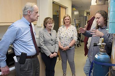 Dr. Michael Gitcho (left) updates US Sen. Tom Carper on Alzheimer research. Drs. Melissa Harrington and Sabrina McGary listen.