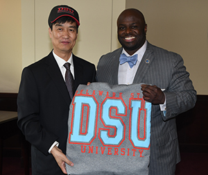 Dezhou University Chairman Liu Wenlie (l) show hat and blanket gifts presented by Provost Tony Allen (r),