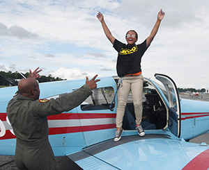 An elated 16-year-old Dominica Thomas celebrates completion of her first solo flight along with her dad Maj. Kenneth Thomas.