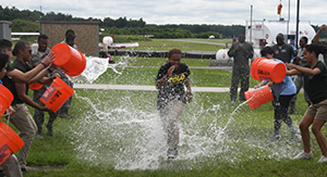 Dominica Thomas runs through the traditional water gauntlet that each young pilot ran through upon completing their solo flight.
