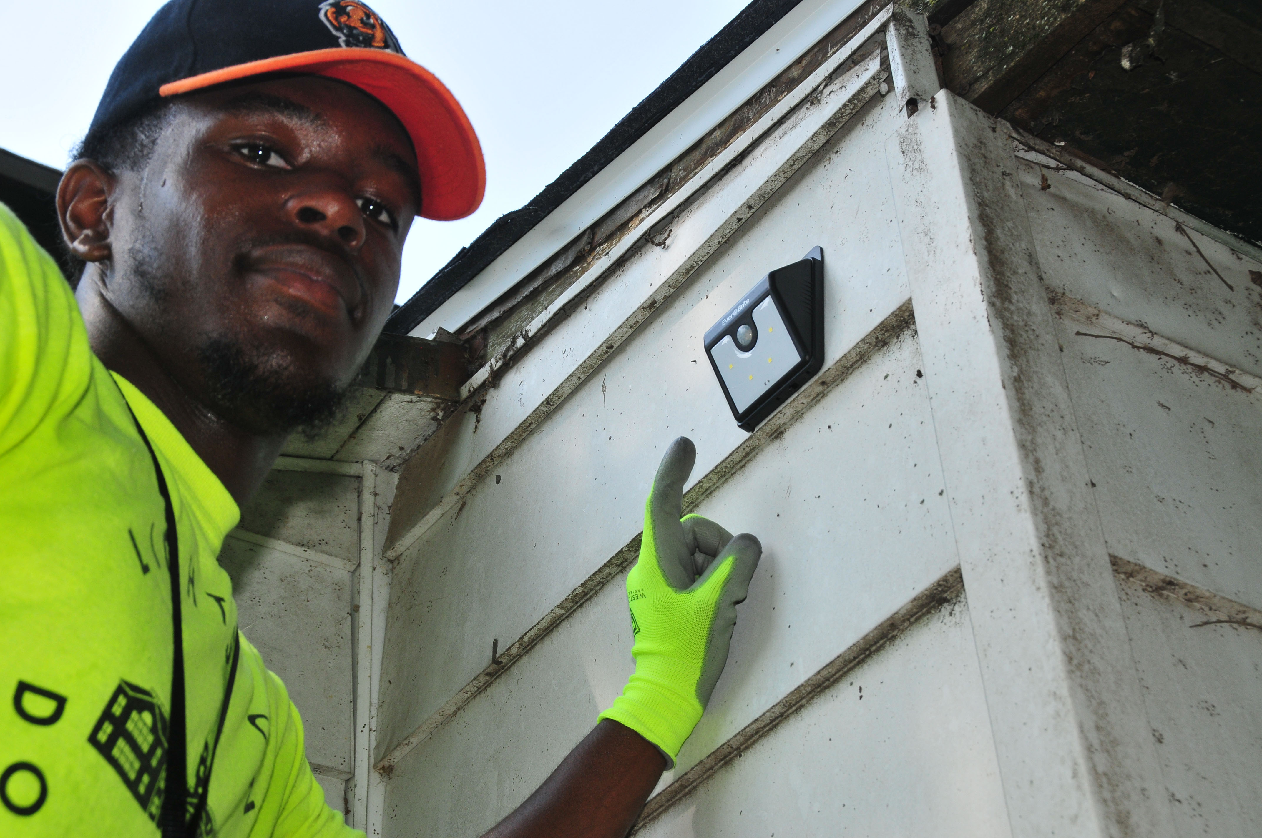 DSU student Eric Wright points to a motion floodlight he just installed at a Dover home.