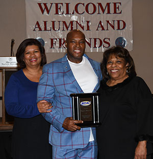 Ronnie Shaw Sr. (center) with his wife Linda (l) and University President Wilma Mishoe.