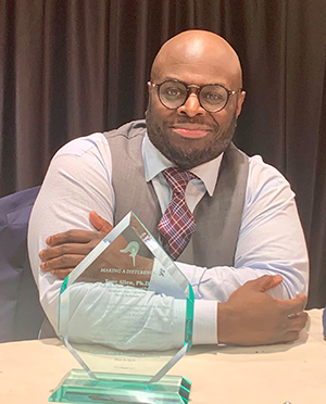 """Provost Tony Allen possess with his """"Make a Difference Award"""" he received after he gave a keynote address at the HBCU Summit."""