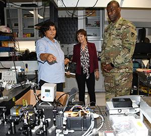 Dr. Renu Tripathi (l) shows Dr. Melissa Harrington and Maj. Gen Cedric Wins the array of optics technology she works with.