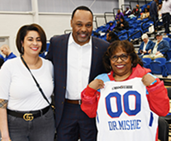 Dr. Wilma Mishoe shows off her Blue Coat basketball shirt with Jackie Griffith and James Collins.