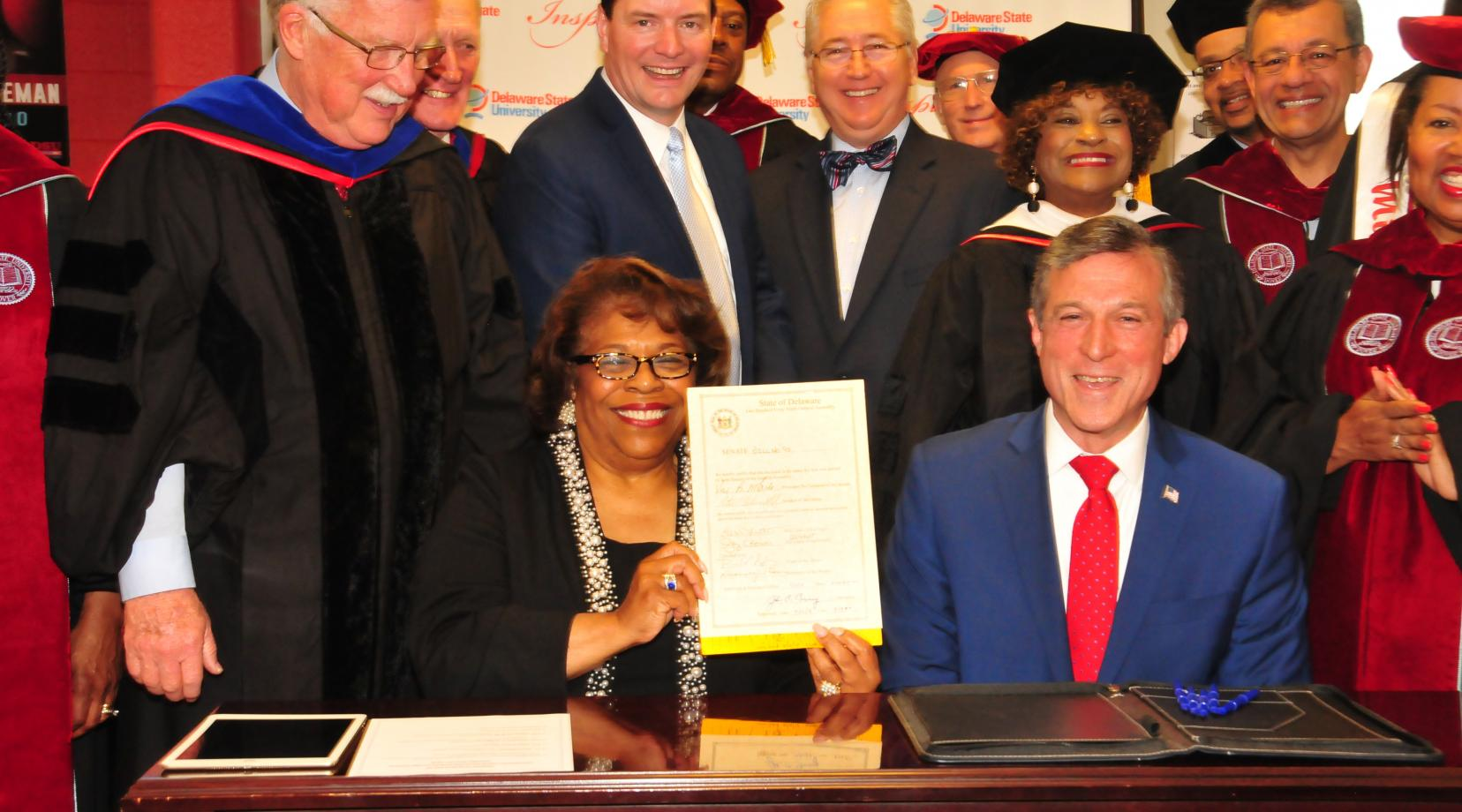 Interim DSU President Wilma Mishoe holds the legislation just signed May 12 by Gov. John Carney (seated next to her) that adds a fourth year of state funding to the Inspire Scholarship Program.