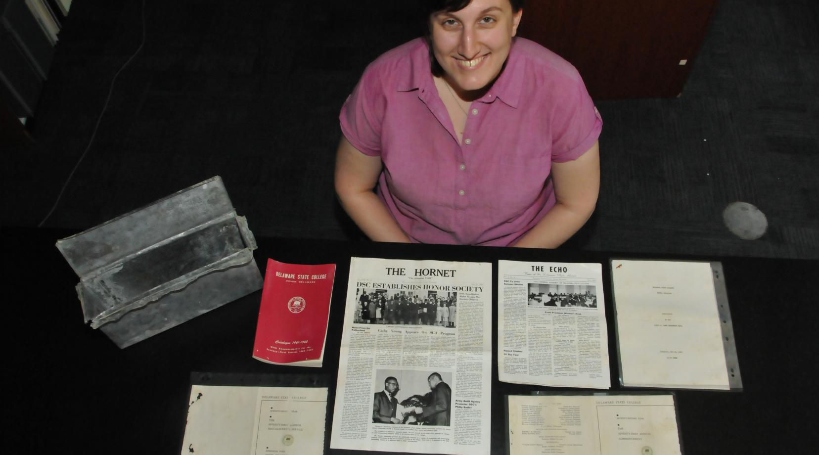 <p>Rejoice Scherry, University archivist, shows the contents of the 1957 Laws Hall time capsule that was recently extracted and opened. The building is being demolished to make way for the construction of a new residential hall.</p>