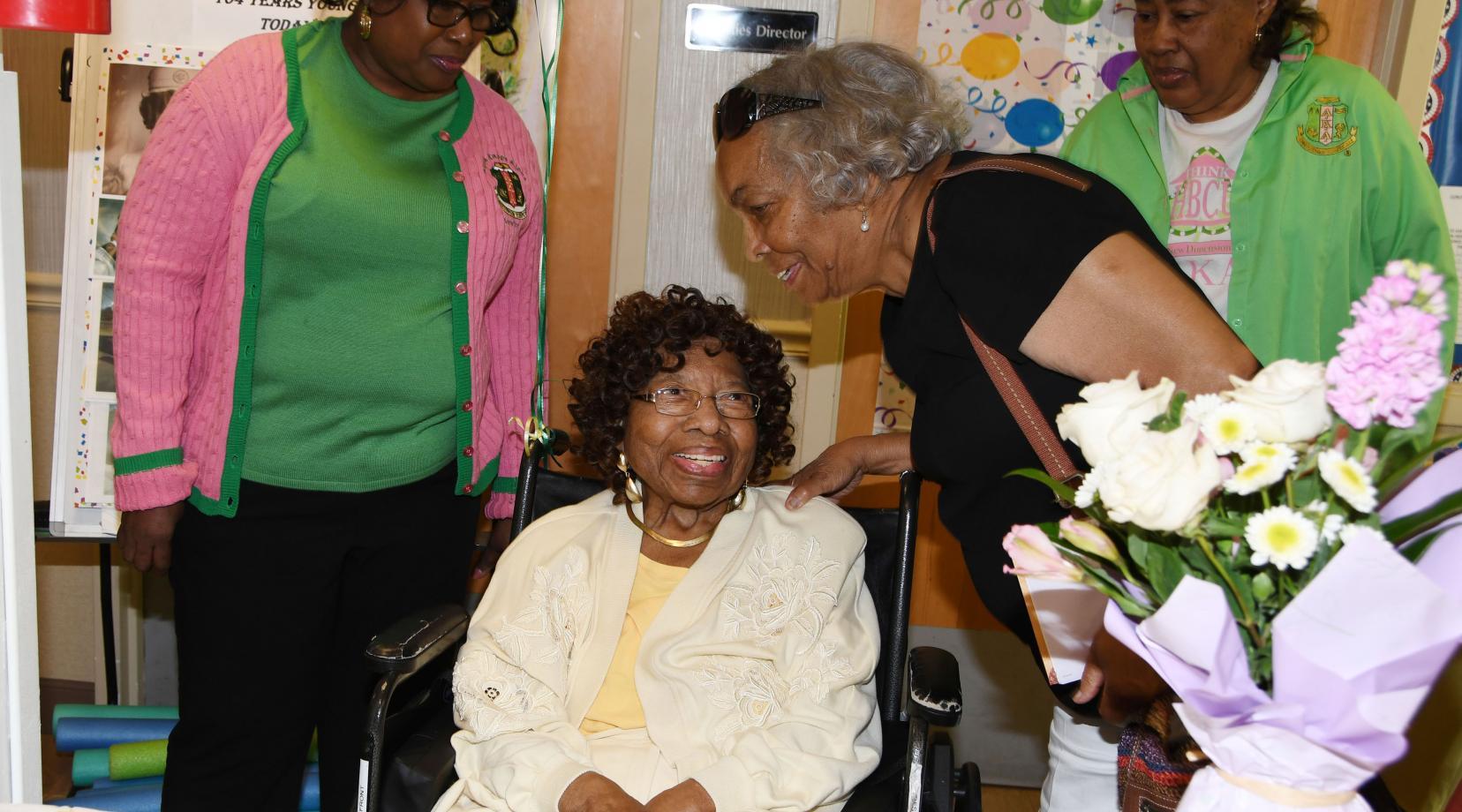 Courtney Stevenson (seated) talks with AKA sorority sister Peggy Swygert at her 104th birthday celebration at the Capital Rehabilitation Center where she lives.