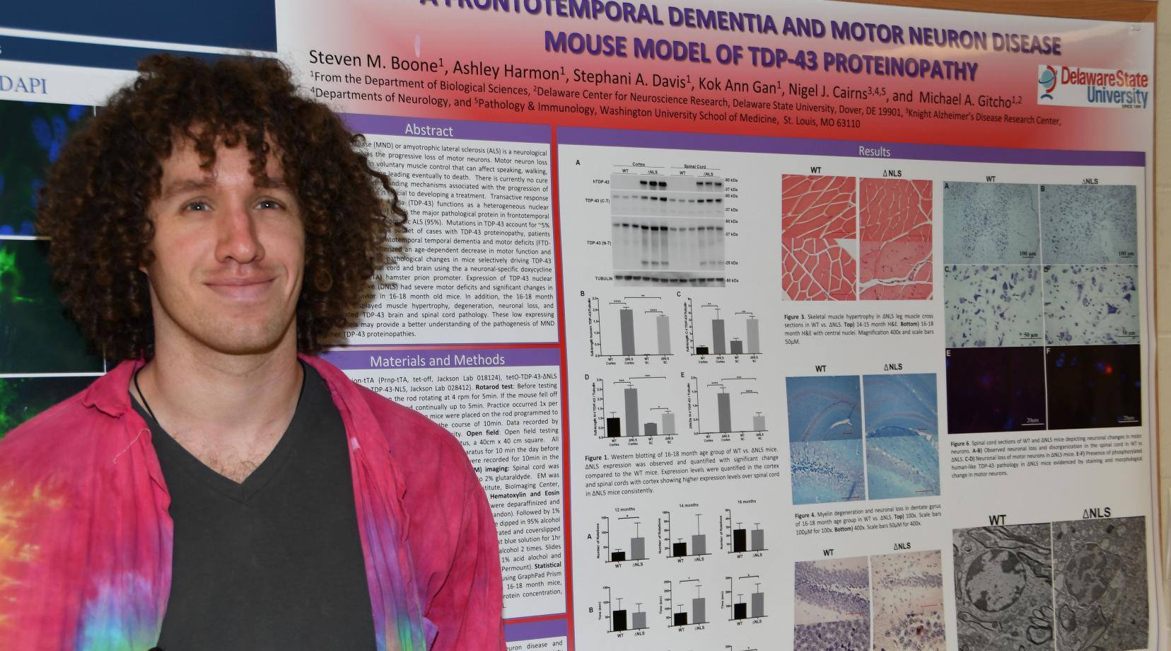 <p>Steven Boone stands alongside a research poster he helped author. The motor neuron disease aspect of the poster is also related to the work he will do for NASA as a research fellow.</p>