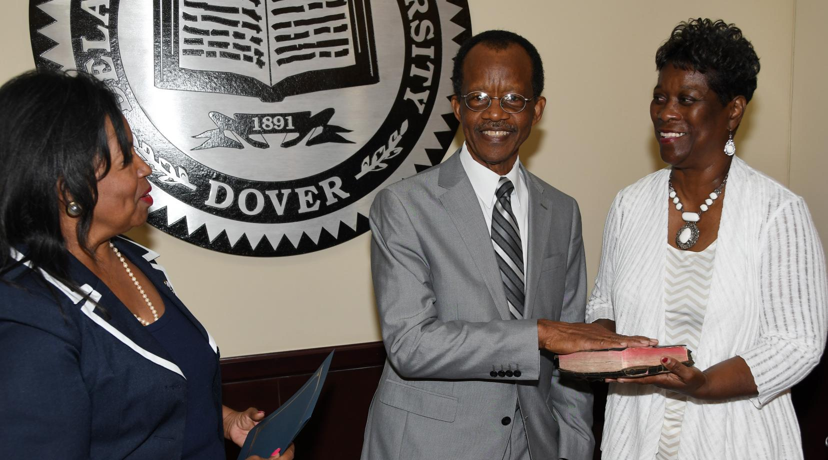 <p>Harold Stafford (center) takes the Board of Trustees oath from Board Interim Chair Devona Williams (l) while his wife Velvia looks on.</p>