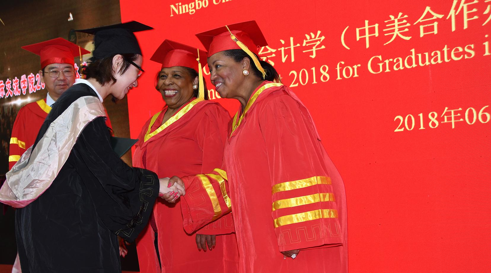 <p>Dr. Wilma Mishoe and Dr. Devona Williams congratulate a graduate during the Commencement ceremony.</p>