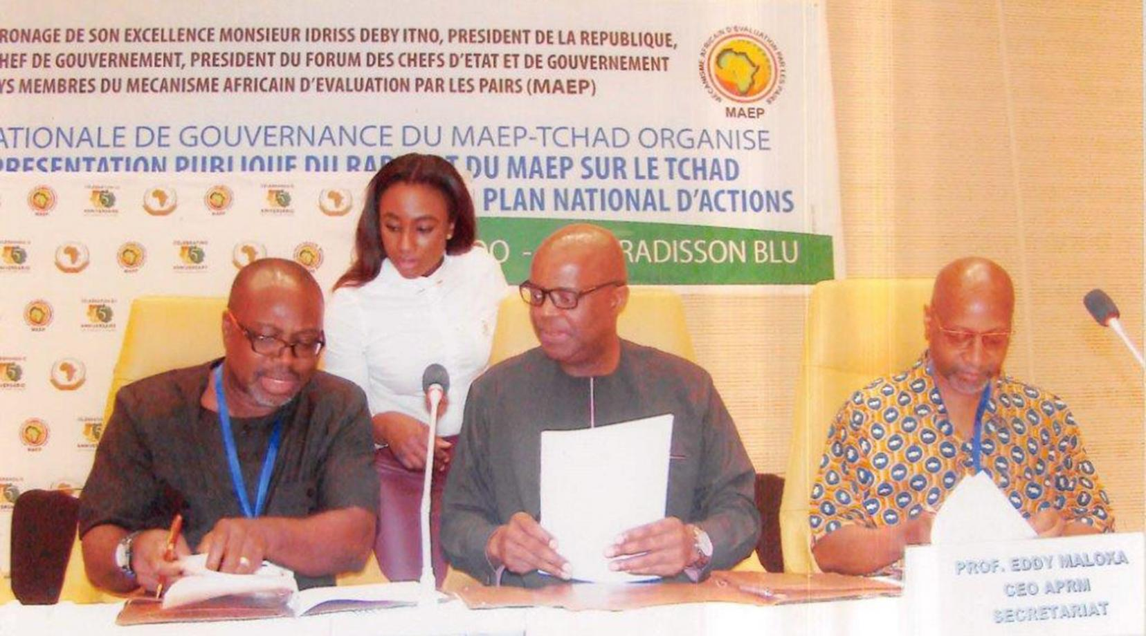(L-r seated)  DSU's Dr. Akwasi Osei, associate dean of the College of Humanities, Education and Social Sciences, Dr. Eddy Maloka, CEO OF APRM, and Ezrah Aharone, DSU adjunct associate professor of history and political science, sign the partnership document in the African country of Chad, while an identified woman assists them.