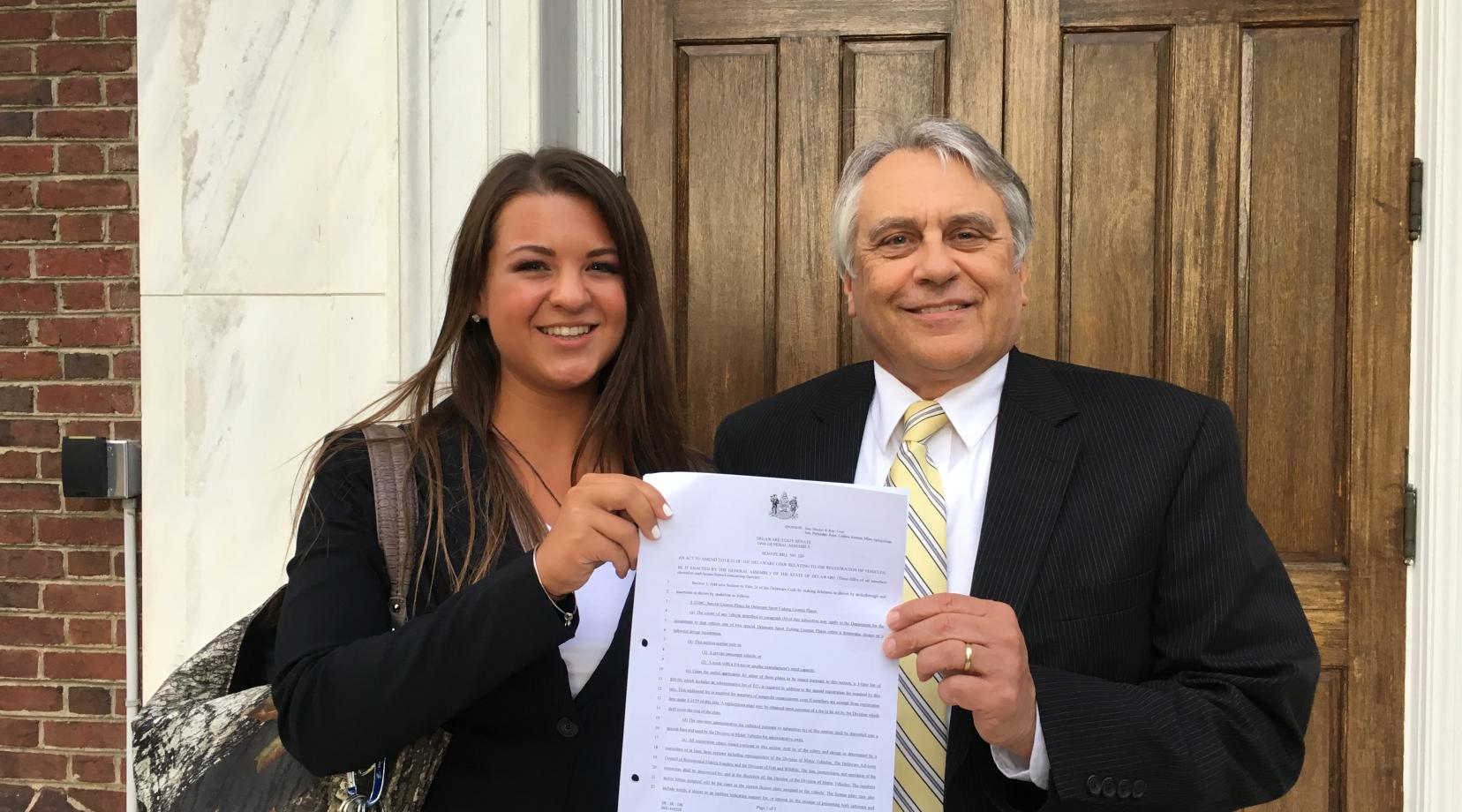 Caitlin Berchtold, a junior DSU fisheries management major, and David Saveikis, director of the state Division of Fish and Wildlife, hold Senate Bill 220 after the House unanimously passed it on June 27. Ms. Berchtold proposed the legislation, which will create license plates of which the proceeds will benefit fisheries research and recreational fisheries.