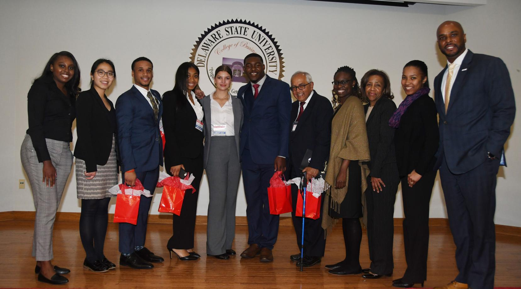 The Gates visitors pose with the Project LEAD Business Case Competition winners during the College of Business' Deep Day. (L-r) Gates team members, Lillian Williams and Julie Ngyuen; students Chris Whitney-Smith, Coreia Benson, Bianca Jacobson and Tysun Hicks, advisor Dr. Chandrakant P. Ganatra; and American Institute for Research members Deaweh Benson, Dr. Kathy Thompson and Dr. Montrisha Williams, along with Acting Dean Michael Casson Jr.
