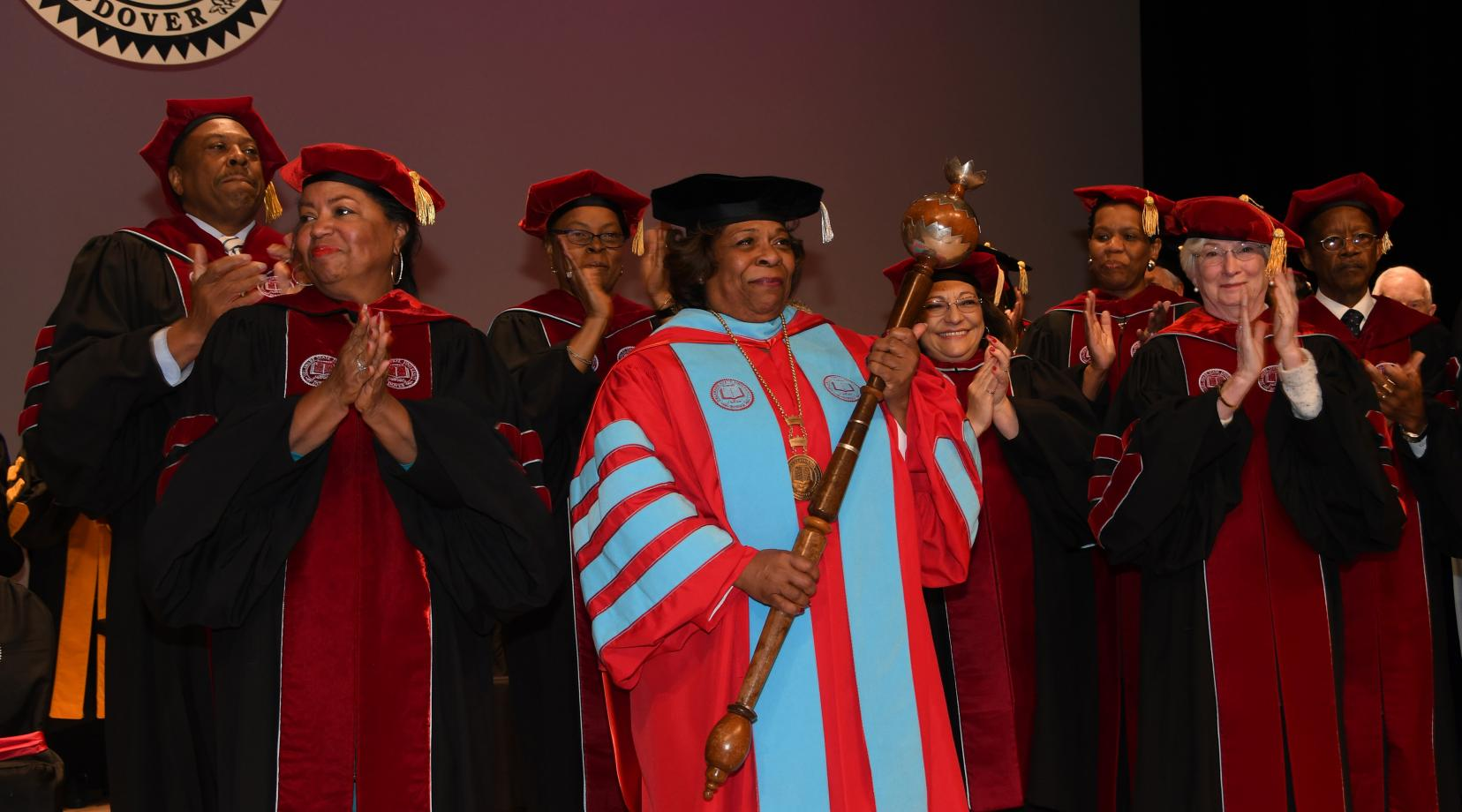 Surrounded by the University's Board of Trustees, the institution's 11th President receives the applause of all those in attendance at the Investiture Ceremony in the Education & Humanities Theatre.