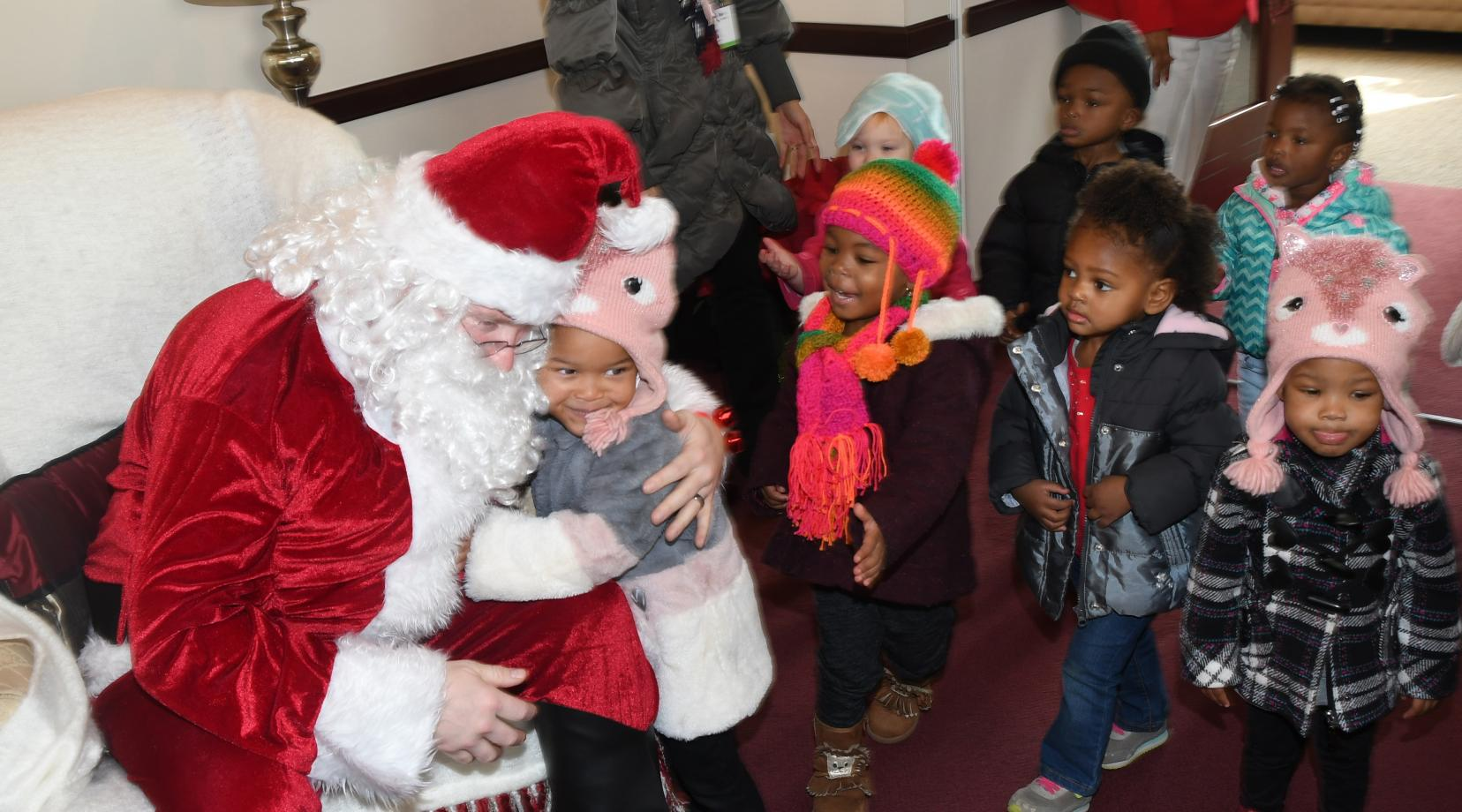 Santa Claus (portrayed by guess who?) greets the young ones of the Child Development Lab in the President's Office on Dec. 13.