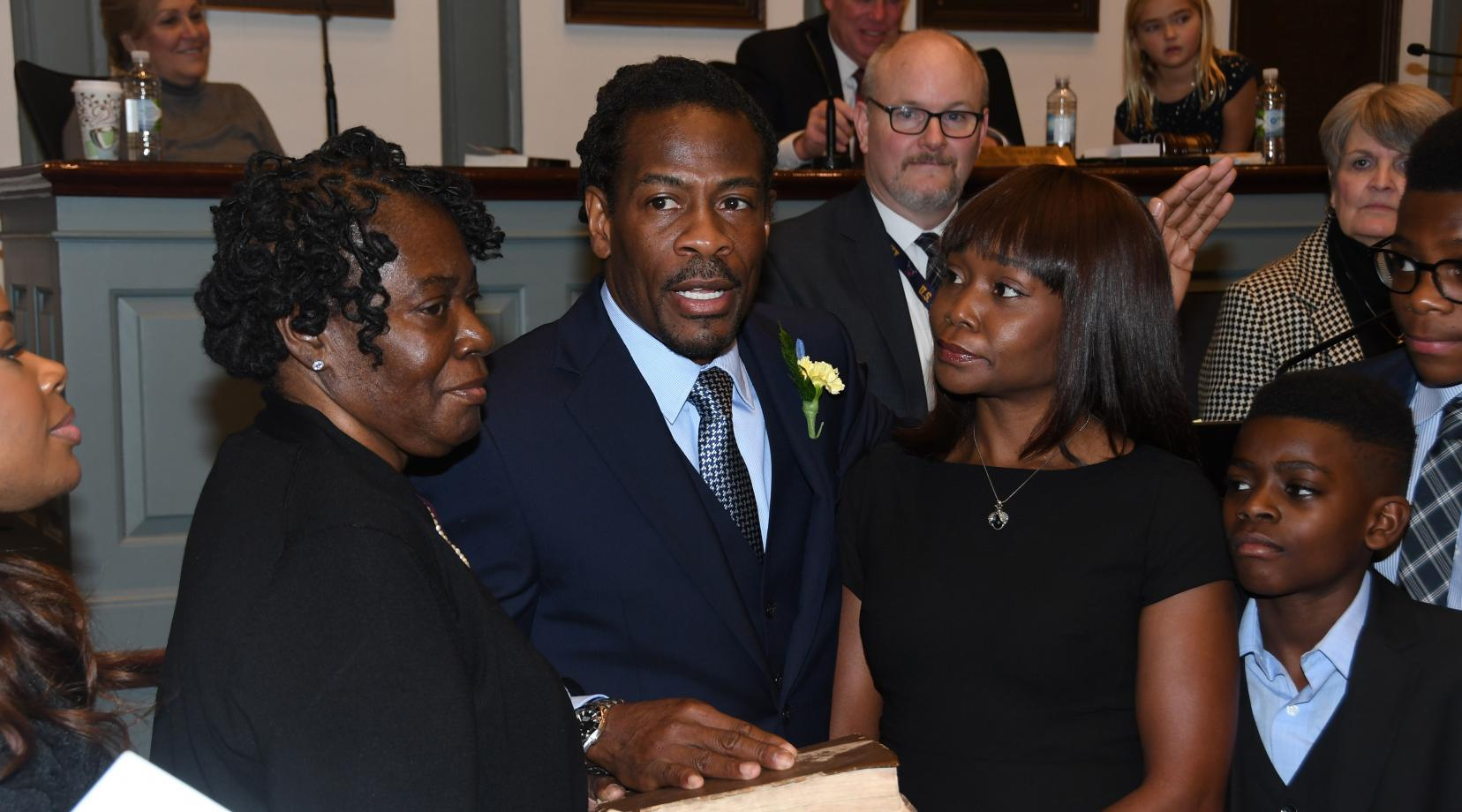 Newly elected Rep. Nnamdi Chukwuocha, surrounded by his family, is sworn in as a member of the Delaware House of Representatives by Delaware Supreme Court Justice James T. Vaughn, Jr. The new legislator's mother Mary Jones (l) holds the bible while his wife Chica stands to his right.
