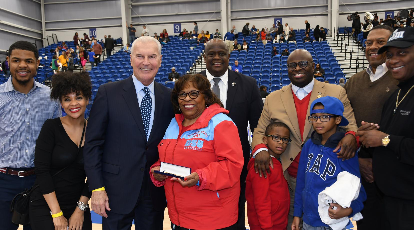 Dr. Wilma Mishoe stands next to Wilmington Mayor Michael Purzycki as she is honored  by the city as part of their annual Black History Month celebration at the 76er Fieldhouse as part of the Long Island Nets vs. Delaware Blue Coats basketball game. Standing around them are city officials and DSU community members.