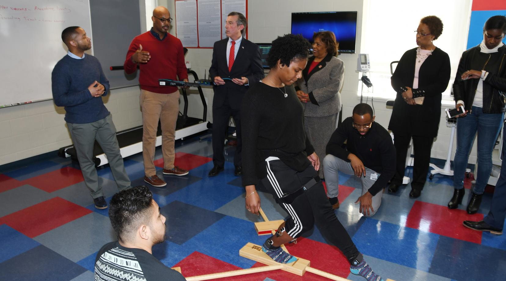 A kinesiology student does movements while electrodes measure electrical activity in her ankle muscles. This predictive injury analysis was part of a Feb. 5 demonstration presented (background l-r) by Dr. Chris Mason and Dr. Von Homer to Gov. John Carney, University President Wilma Mishoe and Dr. Marsha Horton, dean of the College of Health and Behavioral Sciences.