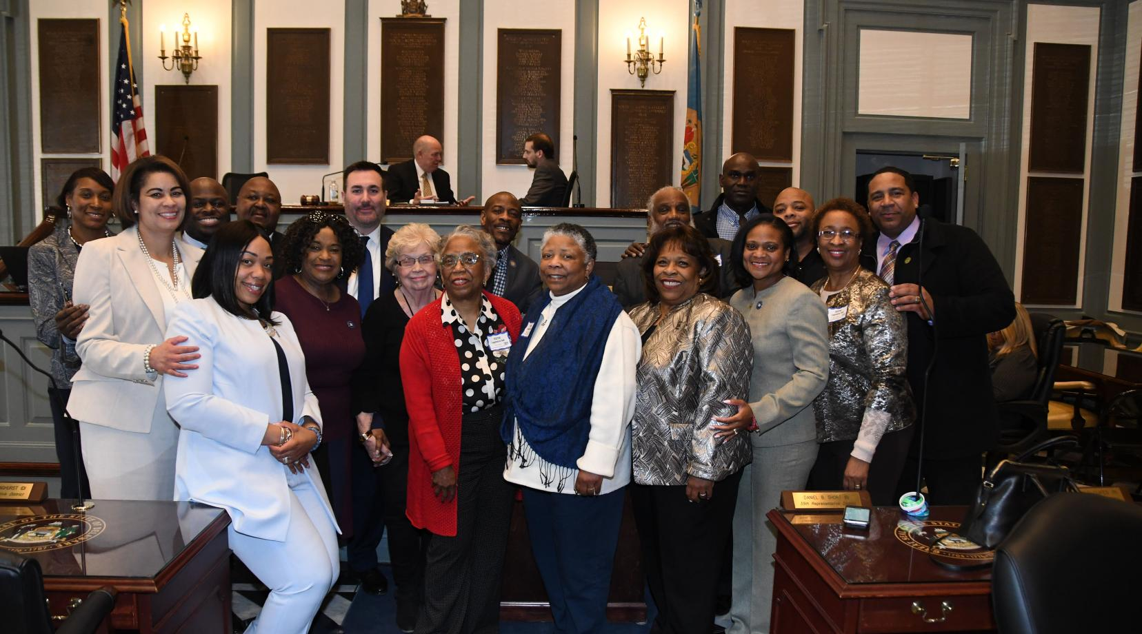 The family of Hattie Mishoe (which include her daughters Bernellyn Carey in the center in red, and to her right Rev. Rita Paige and University President Wilma Mishoe) along with some of the House Joint Resolution No. 2 sponsors and friends celebrate the legislative expression honoring the former First Lady and the wife of then-Delaware State College President Luna I. Mishoe.