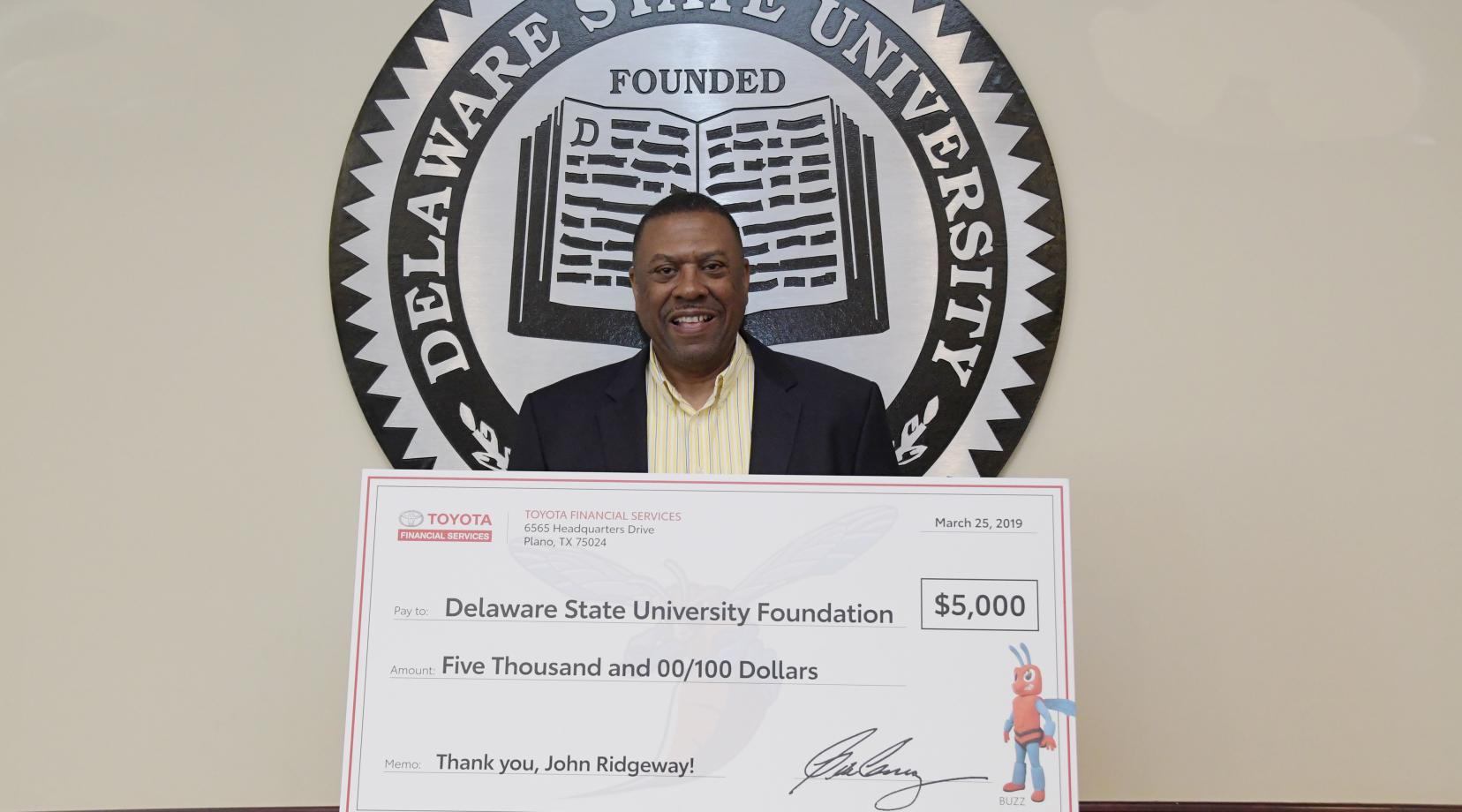 University Board of Trustees Vice Chair John Ridgeway shows a display check of a $5,000 gift presented as a donation by Toyota into an endowed scholarship he established with his wife Sherri. The donation was a retirement gift by Toyota; several other of his work colleague have also donated money into the endowment.