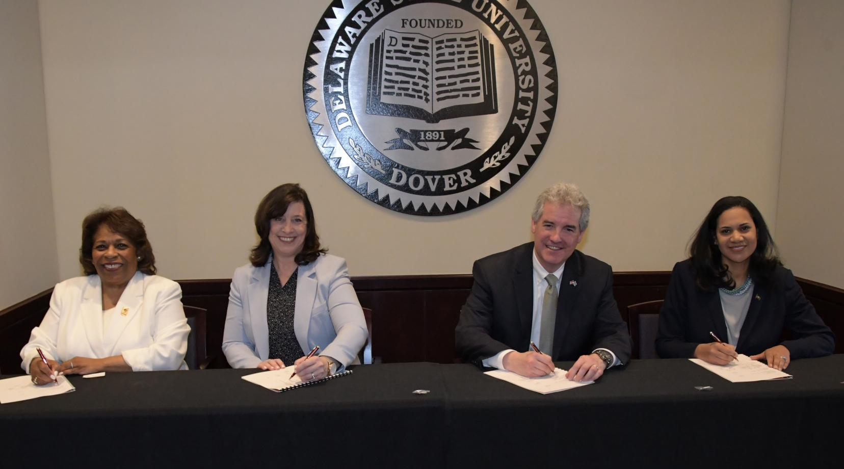 <p>(L-r) University President Wilma Mishoe, EPA Deputy Director Cinday Caporale, DNREC Secretary Shawn M. Garvin and DHSS Secretary Kara Odom Walker sign a new agreement that will provide Delaware State University students internship and research opportunities as well as promote environmental stewardship at the institution.</p>