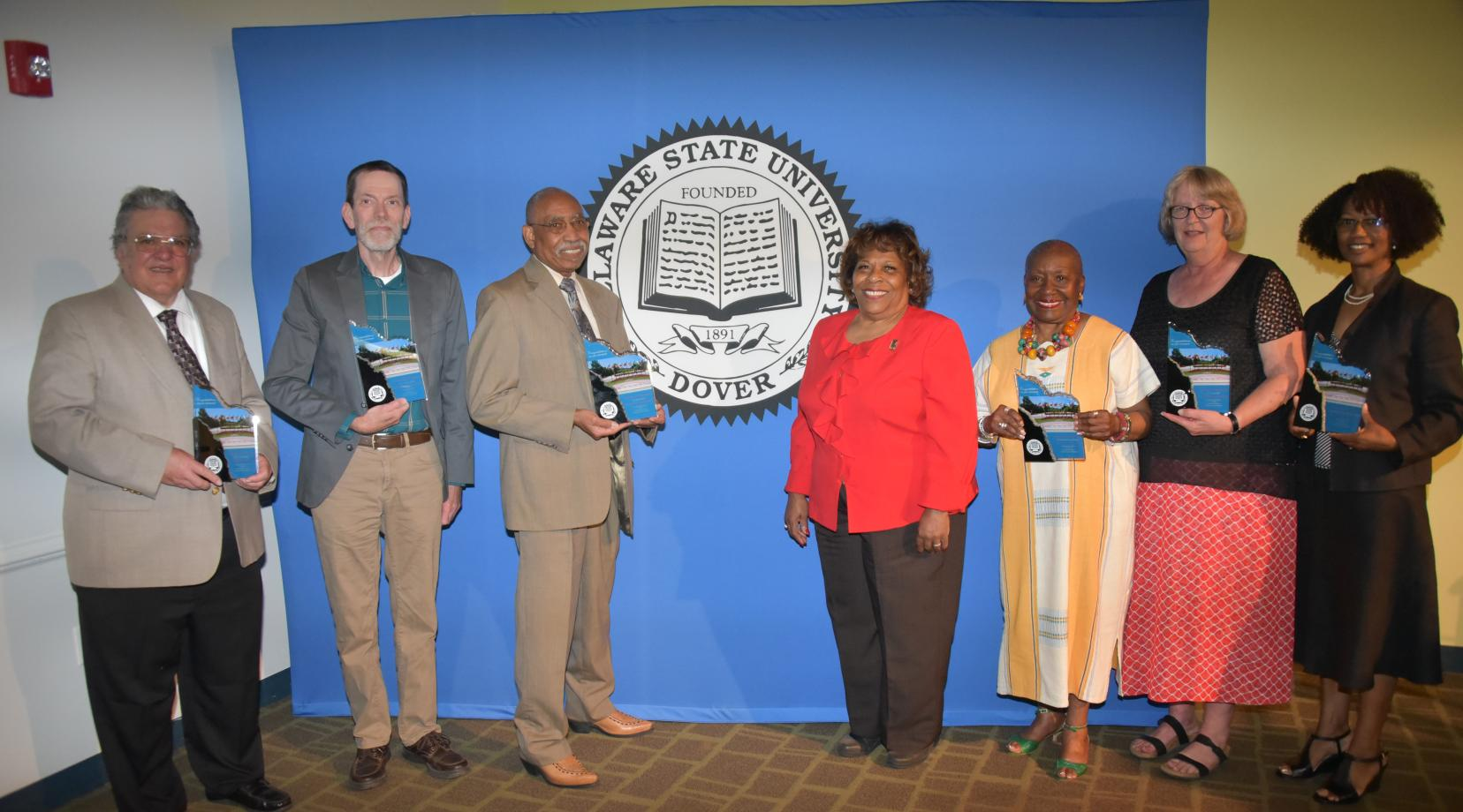 (L-r) 2018-2019 retirees Dr. Peter DiMaria, Dr. Andrew Lloyd, Dr. John Austin, University President Wilma Mishoe (who unretired herself to be the institution's CEO), Dr. Dolores Finger Wright, Dr. Janet Hill and Dr. Sheridan Quarless Kingsberry.
