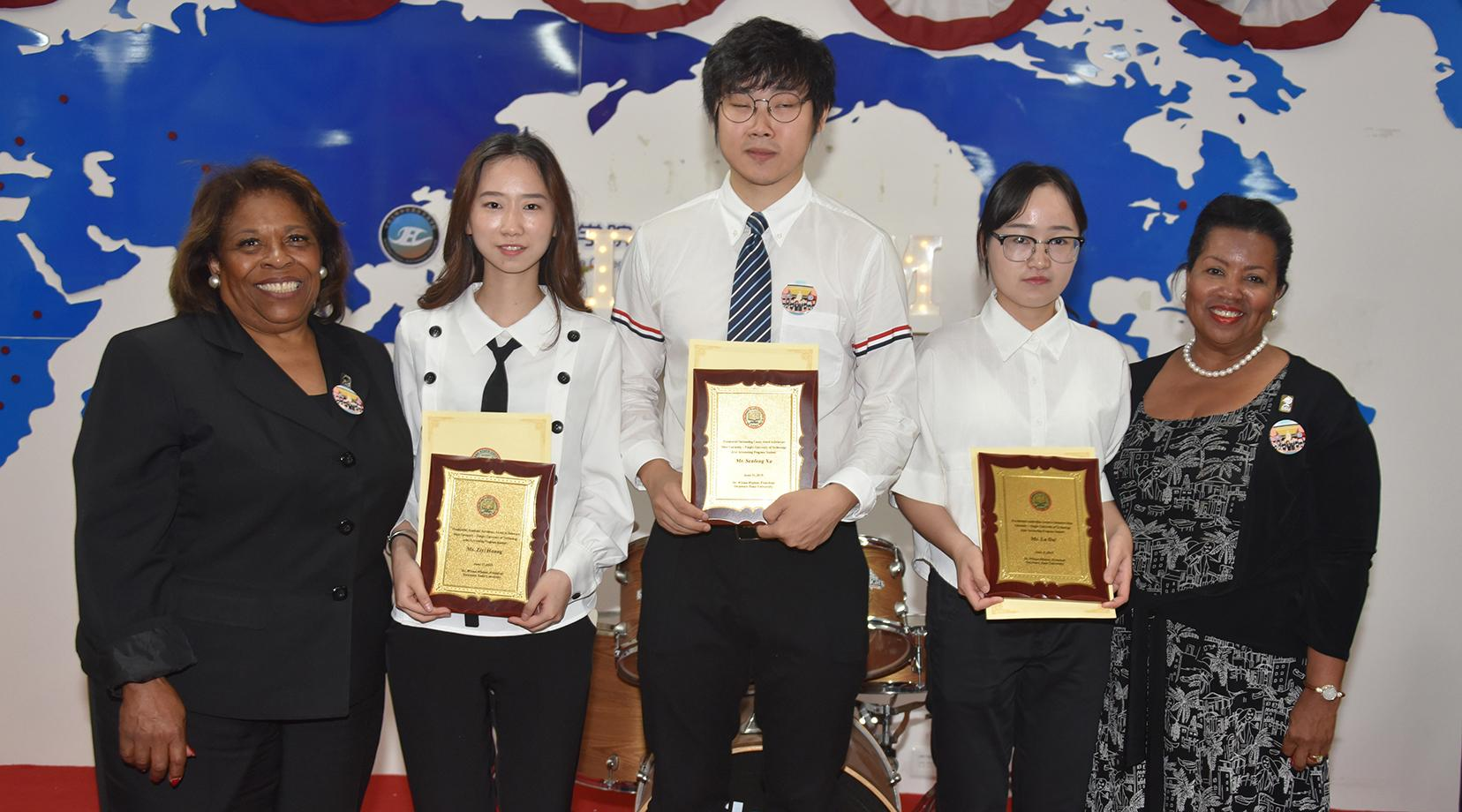 <p>Three students – Ziyi Zhang, Senfeng Xu and Lu Dai – were presented with Delaware State University's Presidential Academic Excellence Award. They are pictured with Dr. Wilma Mishoe and Dr. Devona Williams.</p>