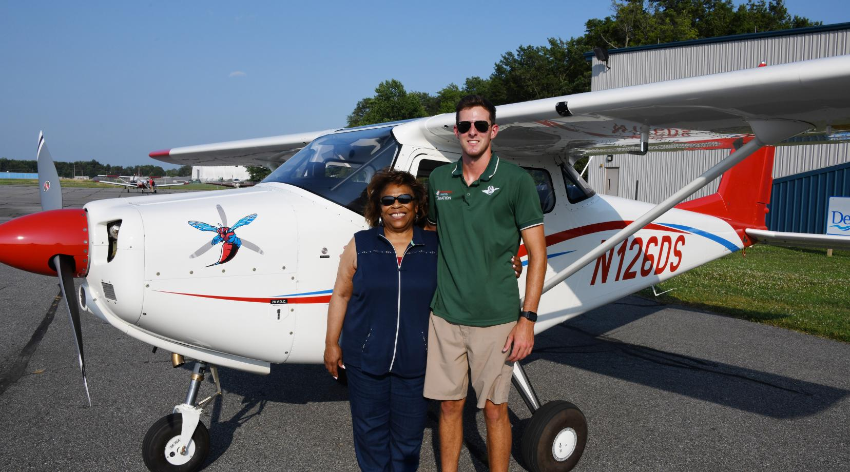 <p>DSU President Wilma Mishoe poses with Aviation Program graduate and current Instructor B. Lane DeLeon after flying into the Delaware Air Park on the first aircraft of a new fleet planes for the University.</p>