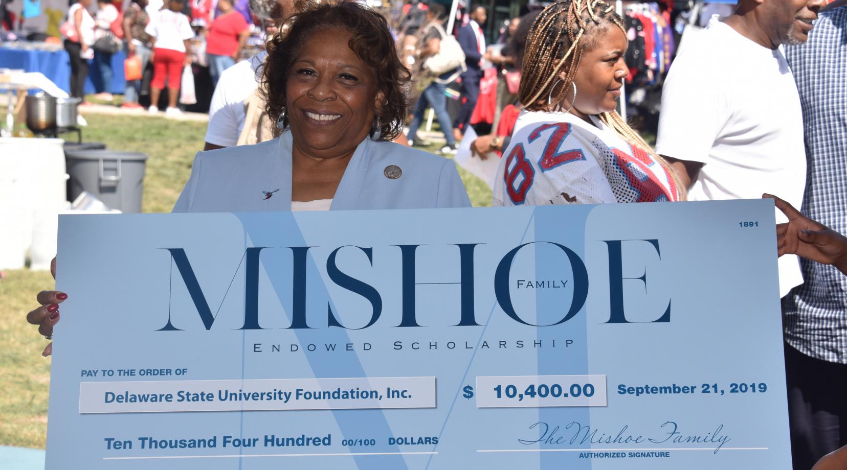 University President Wilma Mishoe holds a display check on behalf of her family that signals the establishment of the Mishoe Endowed Scholarship.
