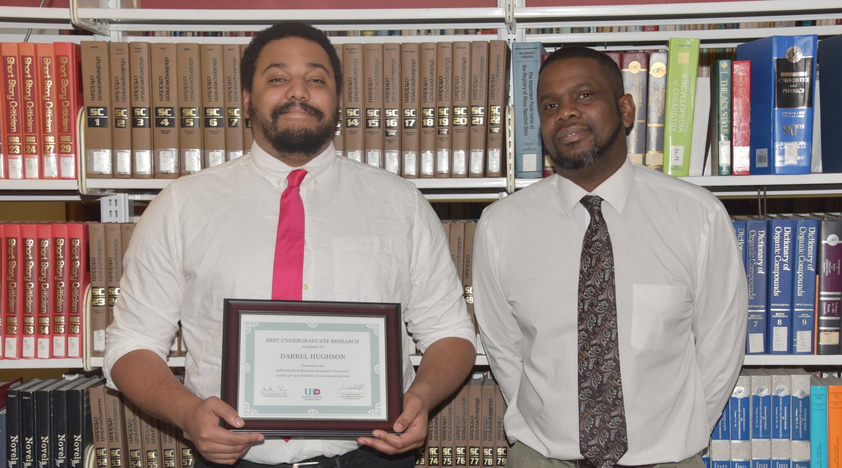 Darrell Hughson,(r), a junior English major, recently took the $500 first-place in a research presentation competition in a national symposium in Houston, Texas.