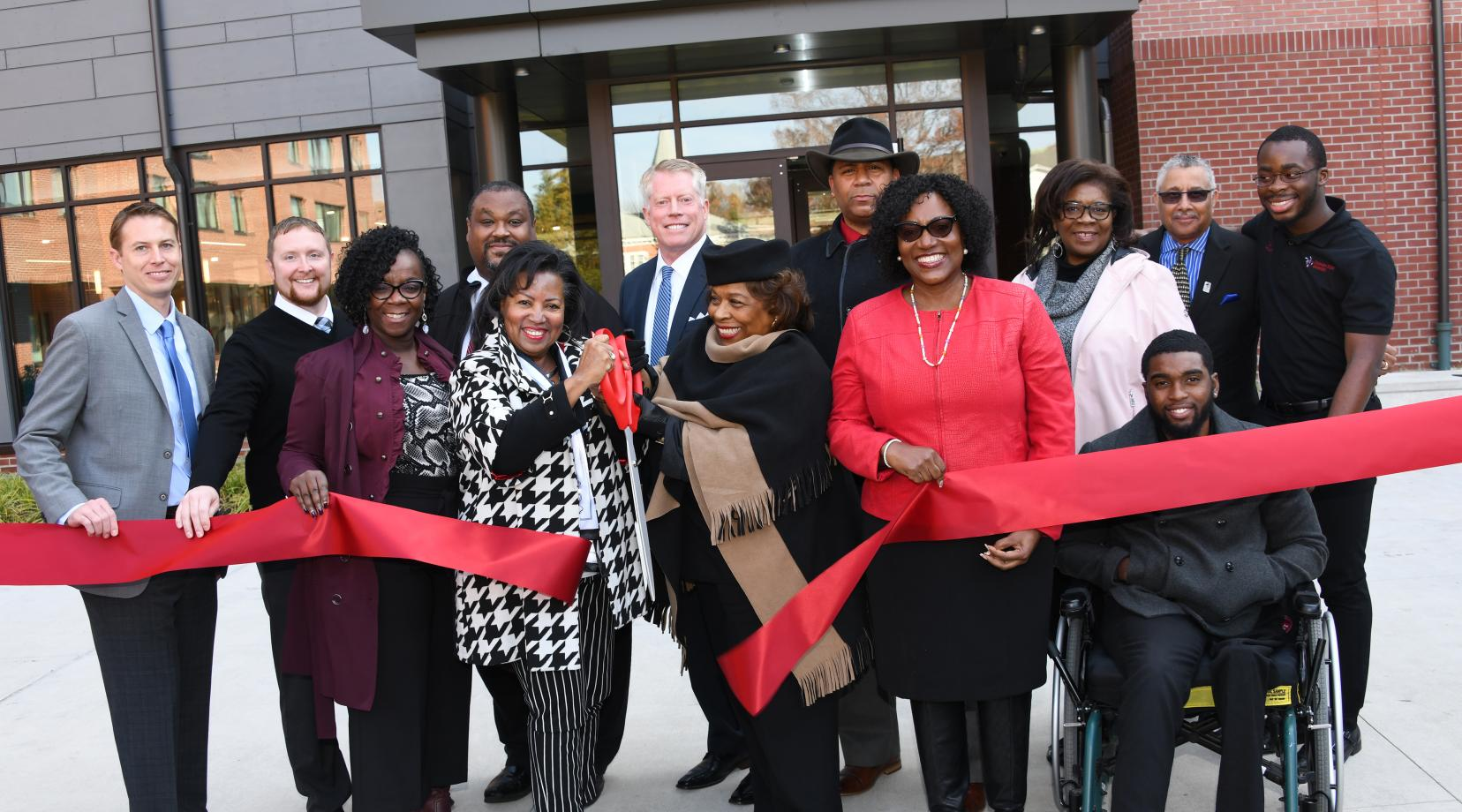 Dr. Devona Williams (with scissors) and University President Wilma Mishoe and others take part in the ribbon-cutting ceremony to formally christen the new Tubman-Laws Residential Hall.