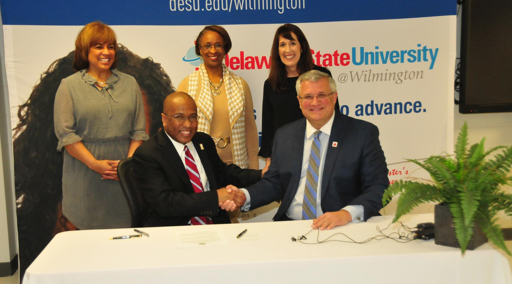DSU President Harry L. Williams shakes hands with Red Clay School District Superintendent Merv Daugherty after signing an agreement to offer IT courses to high school students at DSU@Wilmington.