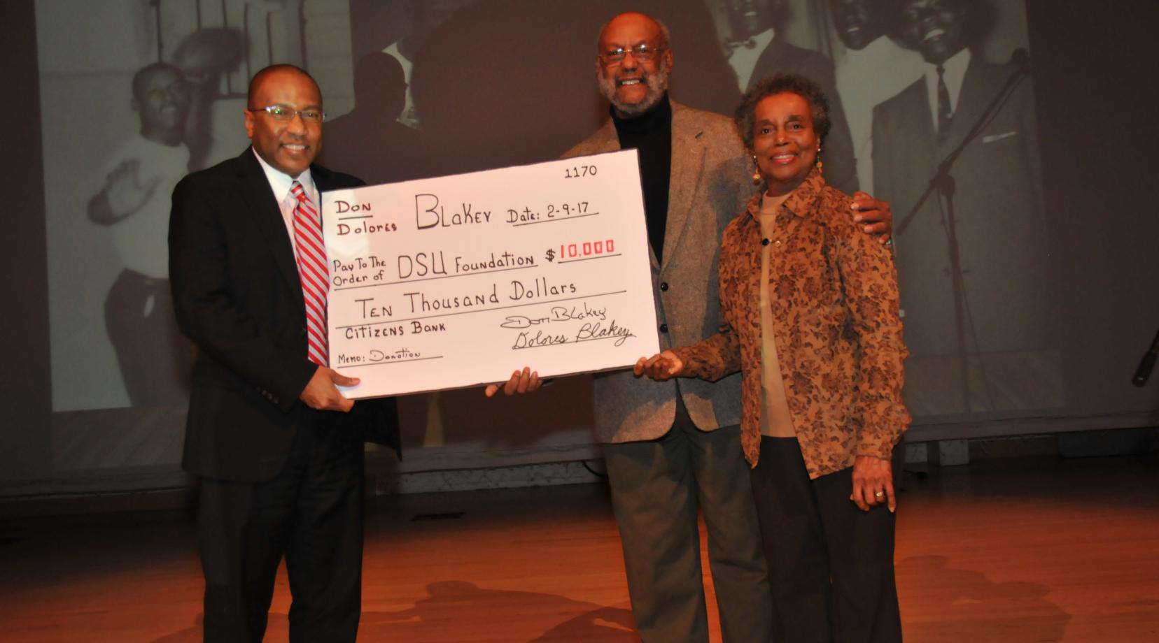 <p>DSU President Harry L. Williams holds up a symbolic check representing a donation of $10,000 by Dr. Donald and Dolores Blakey (right and center), classes of 1958 and 1962, respectively. The check was presented during the Feb. 9 Founders Day Program.</p>