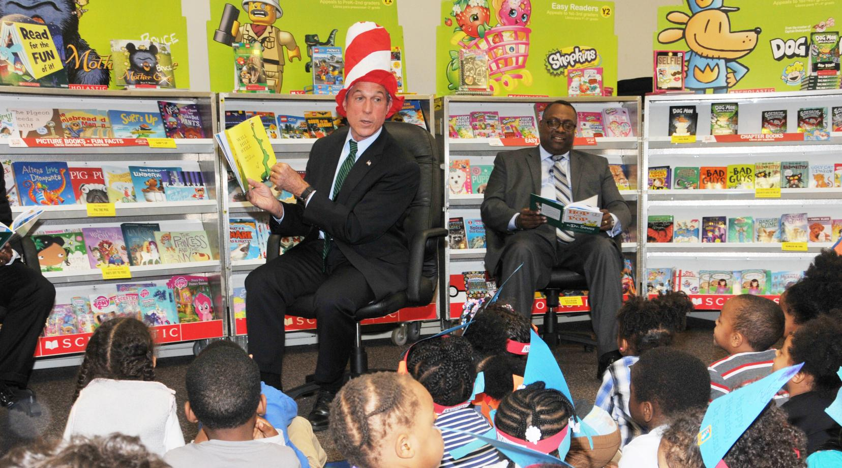 Gov. John Carney reads to the children, while Tyrone James of the United Way of Del. also reads along.