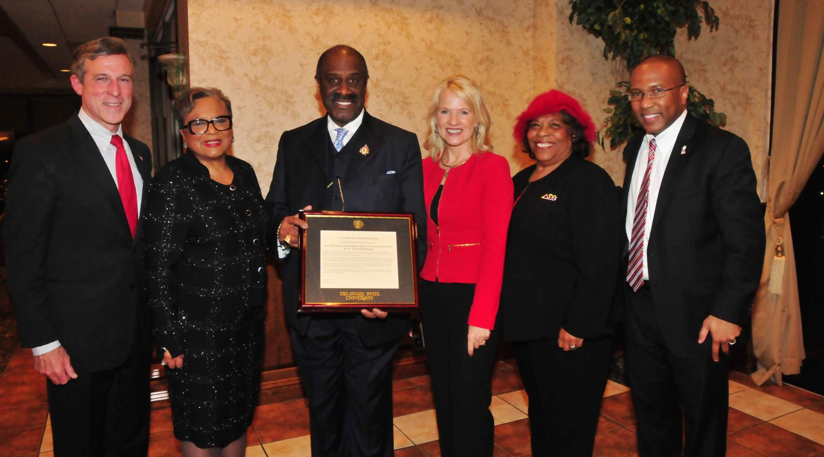 (L-r) Gov. John Carney, Rev. Dr. Jessica Kendall Ingram and her husband Bishop Gregory G.M. Ingram, Lt. Gov. Bethany Hall-Long, DSU Board of Trustees member Wilma Mishoe and DSU President Harry L. Williams, who presented the Ingrams with commendation from DSU.