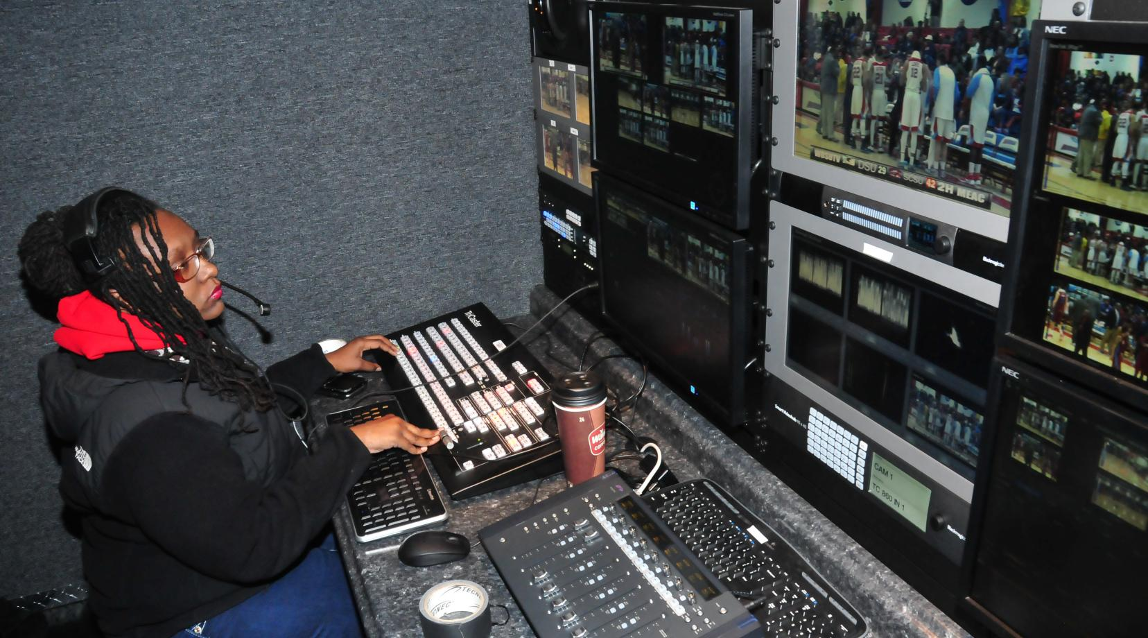Jasmine Alford works a Hornet basketball game in the Mobile Video Production Trailer. The production trailer has reduced the set-up time for the students and provided them with an excellent hand-on experience environment.