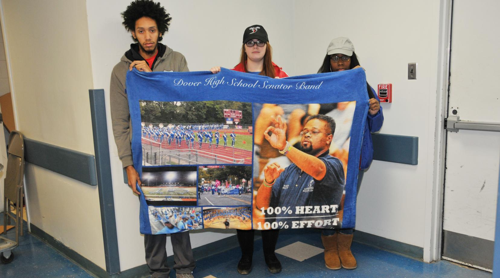 <p>(L-r) Carlos Ortiz, Christina Trice and Akeya Rainer, former Dover HS Band members who were under Lenny Knight's director and then followed him to DSU, hold up a blanket of images that Dover HS presented to Mr. Knight at the end of his tenure there.</p>