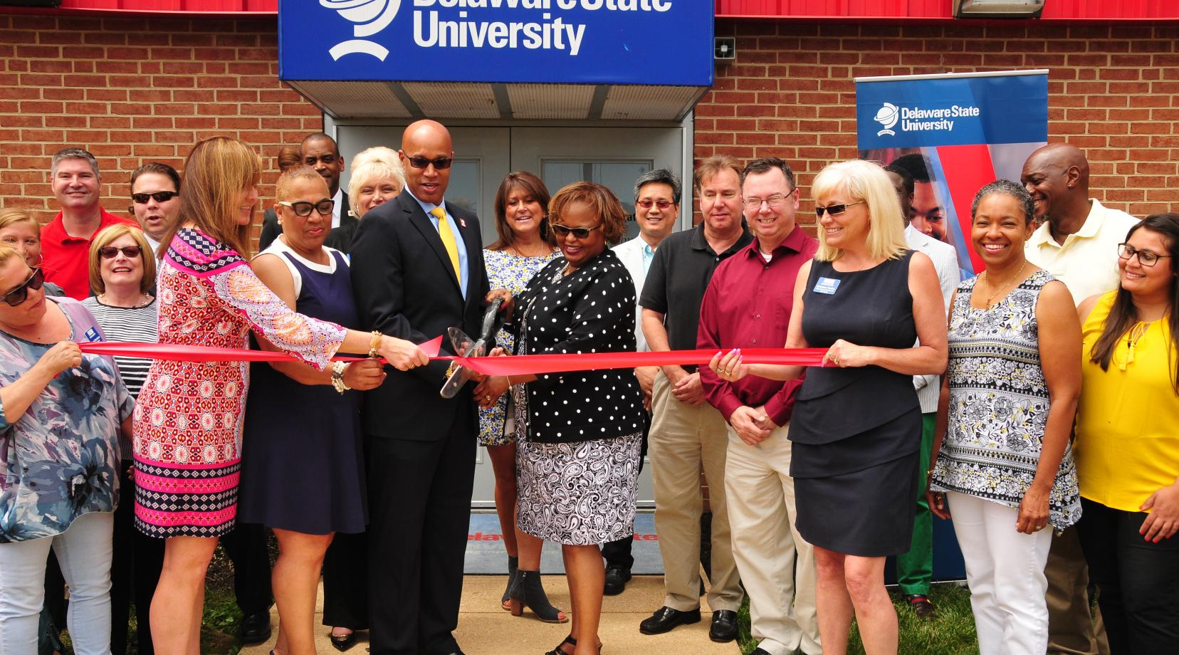 "<p>DSU Board of Trustees member Roy Roper and DSU Chief Financial Officer Teresa Hardee join officials of the New Castle County Chamber of Commerce for a ribbon cutting ceremony at the <a href=""mailto:DSU@Wilmington"">DSU@Wilmington</a> location in recognition of its educational contribution to Northern Delaware.</p>"