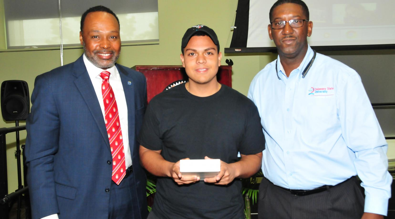 Kevin Coque Alarcon, a freshman mass communications major (center), won a digital drawing and took home an iPad Mini. Standing with him are keynote speaker James Collins (l) and DSU CIO Darrell McMillon.