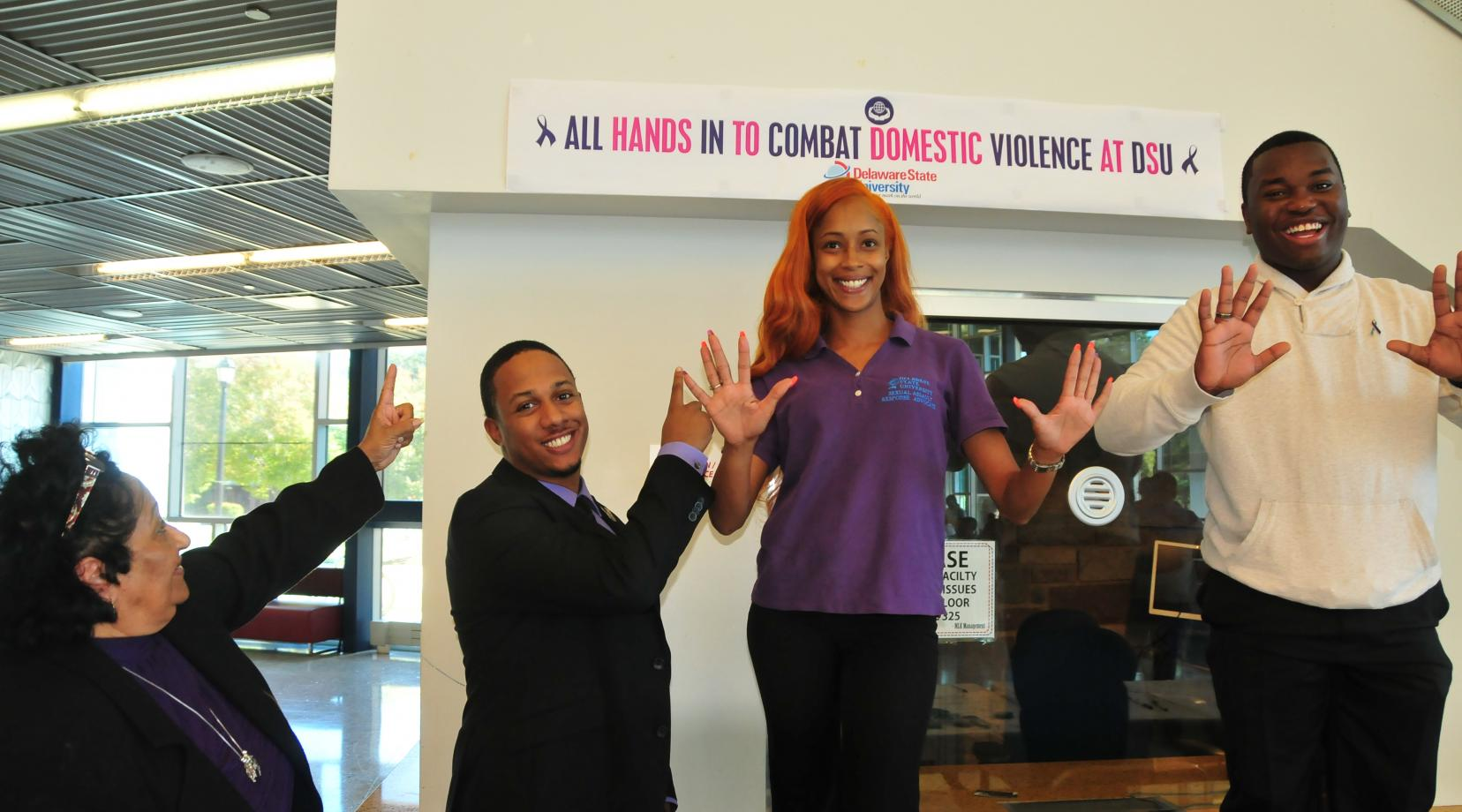 """<p>(L-r)  Dr. Pauline Meek, associate director of the Office of Counseling Services; Kyle Sheppard, SARA member; Silver Debrick, prevention specialist in the DSU Office of Career Services; and Malcolm L. Washington,  SARA member, stand with their campaign theme """"All Hand in to Combat Domestic Violence at DSU</p>"""