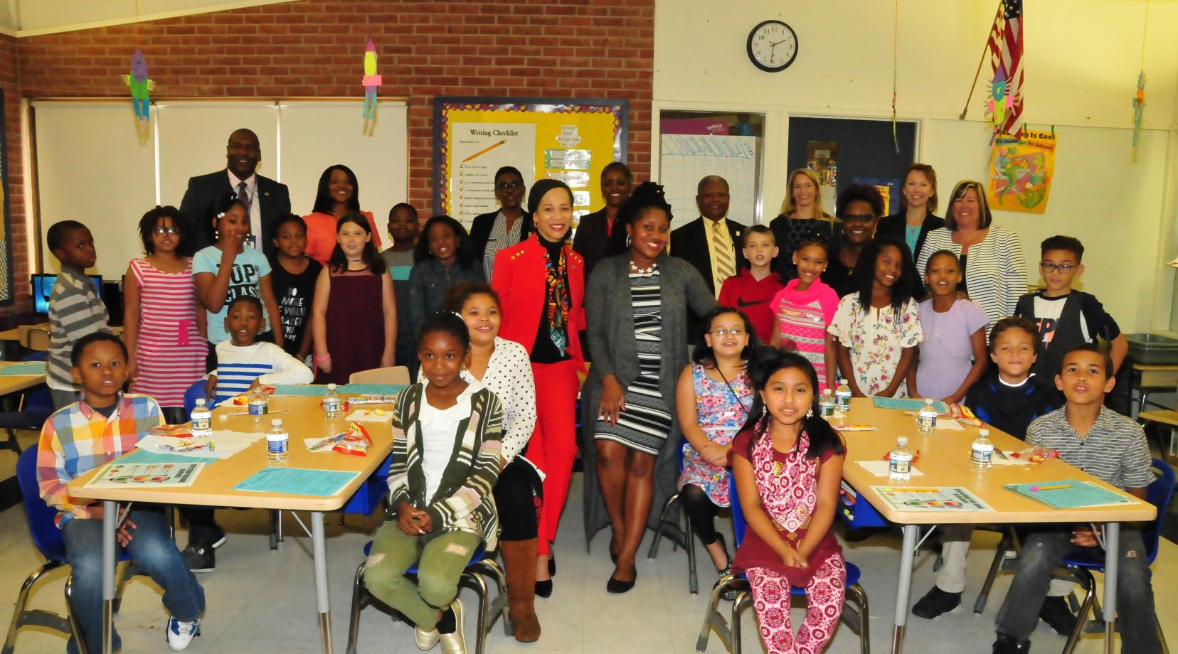 Del. Congresswoman Lisa Blunt Rochester and Ciara Martin, DSU nutrition educator (both in the center),  join students of Towne Point Elementary School and others for a photo after teaching about healthy and unhealthy drink choices.