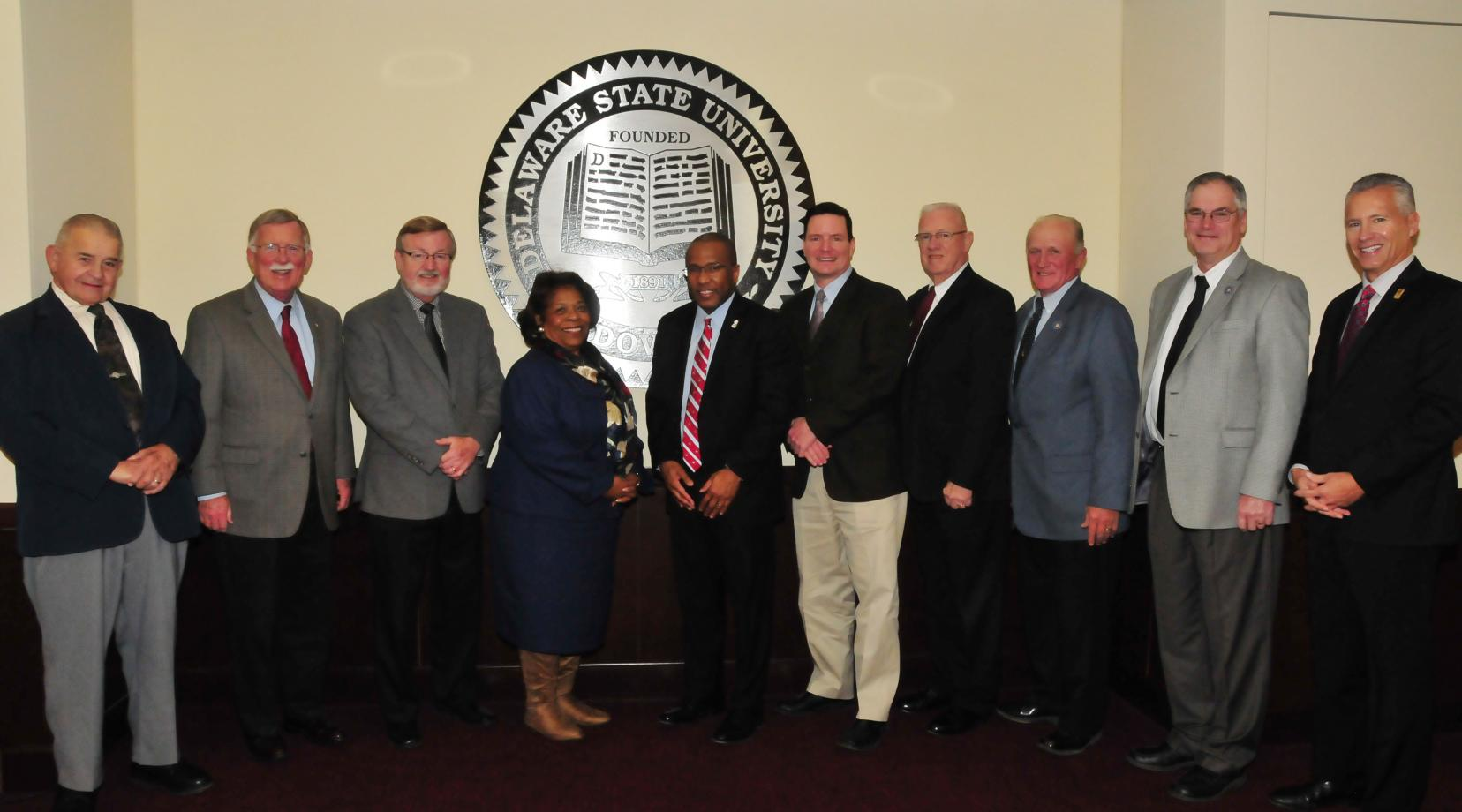 <p>Dr. Harry L. Williams, joined by DSU Board of Trustees Chairwoman Dr. Wilma Mishoe, posed with a group of Kent County state legislators who held their final meeting with the outgoing DSU president on Dec. 12.</p>