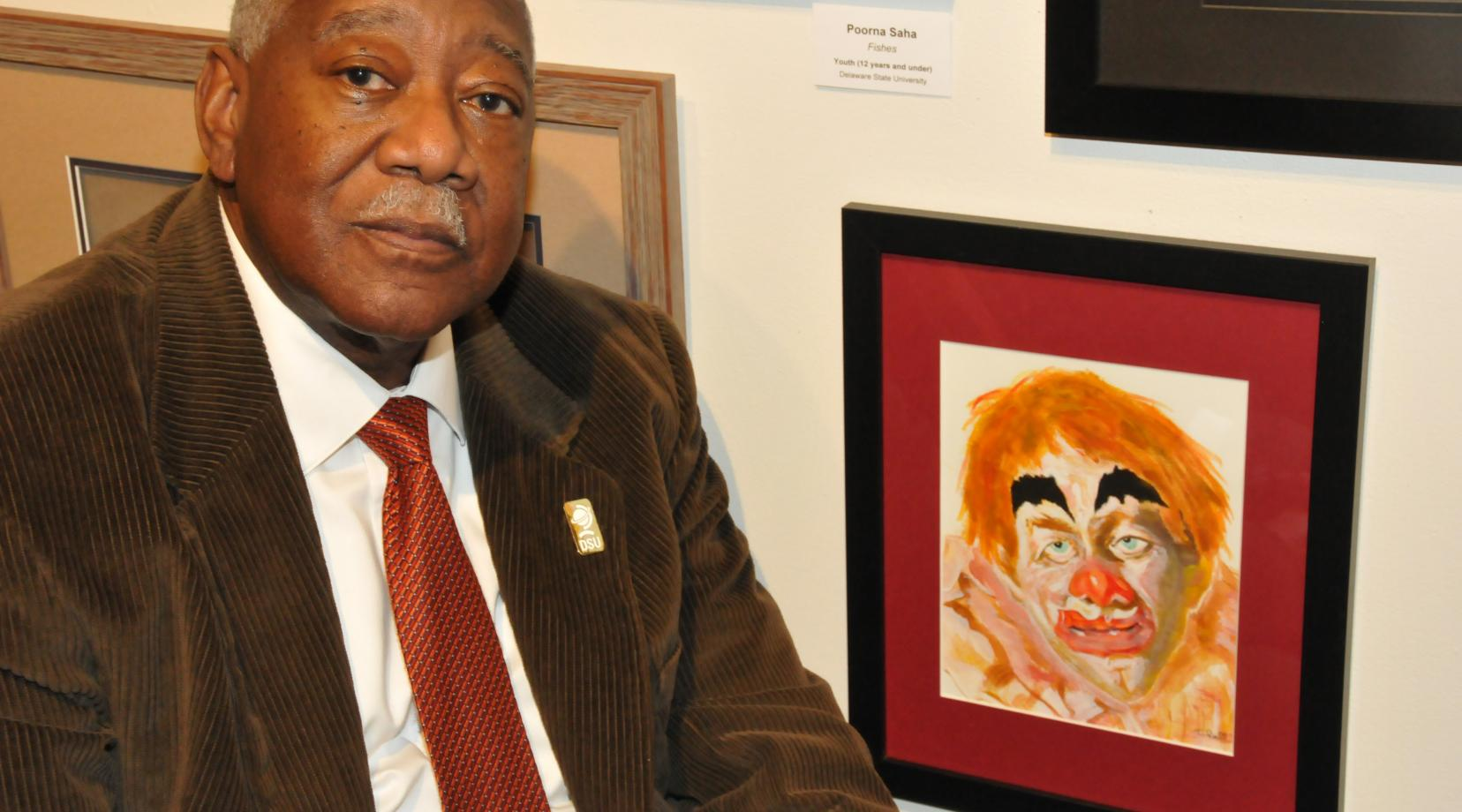 "Bryant T. Bell with his artwork entitled ""Barnum and Bailey Circus,"" one of the more than 200 works on display in the State Employee Exhibition in the Arts Center/Gallery on campus."