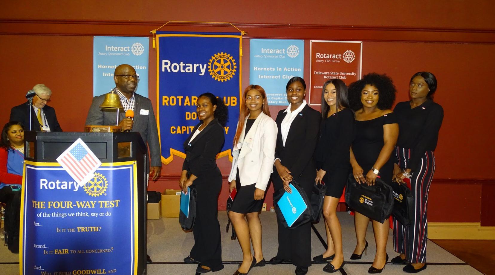 <p>Dr. Esosa Iriowen (r), advisor, introduces the clubs' officers: (l-r) Kasha Hartz (Interact president); Jada Rider (Rotaract president), Francesca Clark (Interact vice pres.), Makila Meyers (Rotaract vice pres.), Sarah Saintaile (Rotaract secretary), and Aanyah Bailey (Rotaract treasurer).</p>